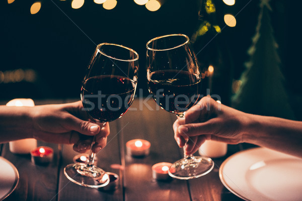 women clinking glasses over served table Stock photo © LightFieldStudios