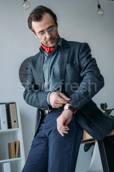 businessman checking wristwatch Stock photo © LightFieldStudios
