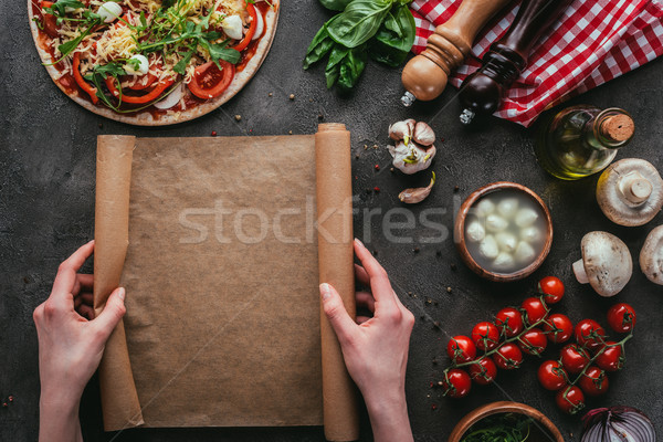 cropped shot of woman with parchent paper preparing homemade pizza on concrete table Stock photo © LightFieldStudios