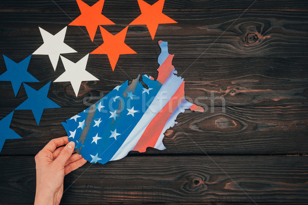 cropped shot of stars and female hand with piece of map with american flag on wooden tabletop, presi Stock photo © LightFieldStudios