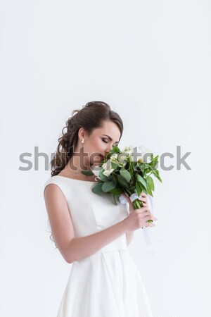 attractive bride with closed eyes sniffing wedding bouquet, isolated on white Stock photo © LightFieldStudios