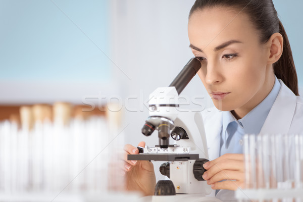 Young concentrated woman scientist working with microscope in laboratory   Stock photo © LightFieldStudios