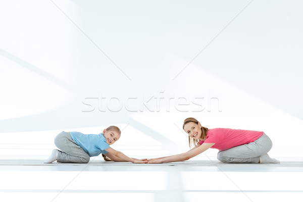 Happy mother and daughter in sportswear exercising on yoga mats and smiling at camera Stock photo © LightFieldStudios