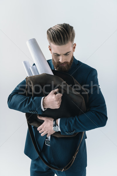 Bearded young businessman holding bag with rolled blueprints on grey Stock photo © LightFieldStudios