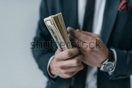 partial view of stylish businessman holding dollar banknotes on grey Stock photo © LightFieldStudios