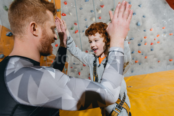 Boy in climbing harness high-fiving dad Stock photo © LightFieldStudios