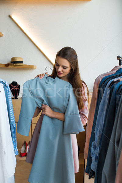 young woman choosing clothes in boutique Stock photo © LightFieldStudios