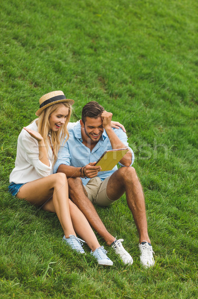 couple with tablet on green lawn Stock photo © LightFieldStudios
