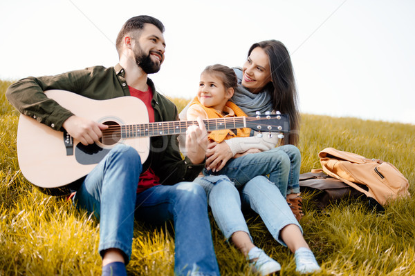Family relaxing on grassy hill Stock photo © LightFieldStudios