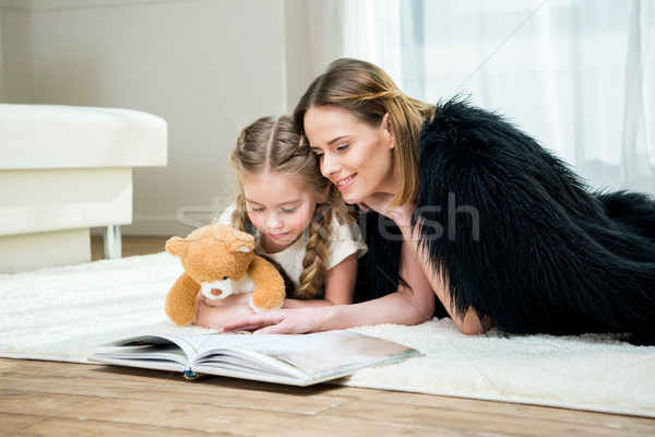 Smiling mother and daughter with teddy bear reading book on carpet  Stock photo © LightFieldStudios