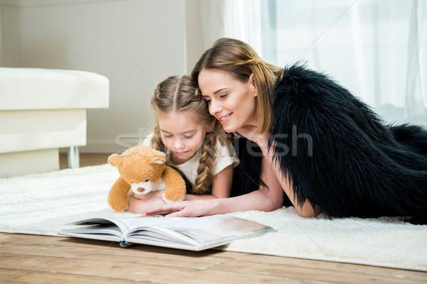 Glimlachend moeder dochter teddybeer lezing boek Stockfoto © LightFieldStudios