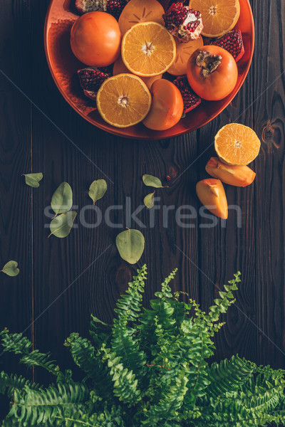 top view of persimmons with cut oranges and pomegranates on plate and green plant on table Stock photo © LightFieldStudios