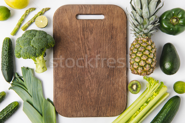 Wooden cutting board with green vegetables and fruits isolated on white background Stock photo © LightFieldStudios