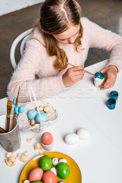 high angle view of cute focused child painting easter egg at table Stock photo © LightFieldStudios