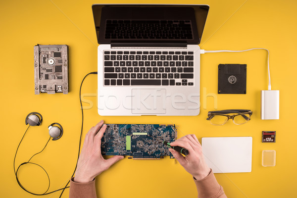 partial top view of person fixing laptop on yellow  Stock photo © LightFieldStudios
