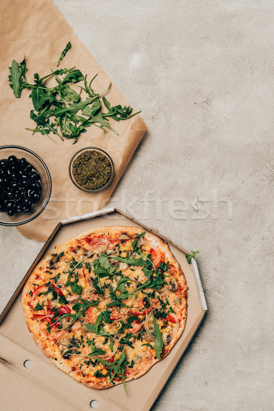 Pizza in cardboard box with toppings on light background Stock photo © LightFieldStudios