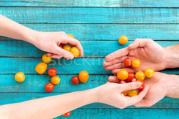 female putting cherry-tomatoes in hands Stock photo © LightFieldStudios
