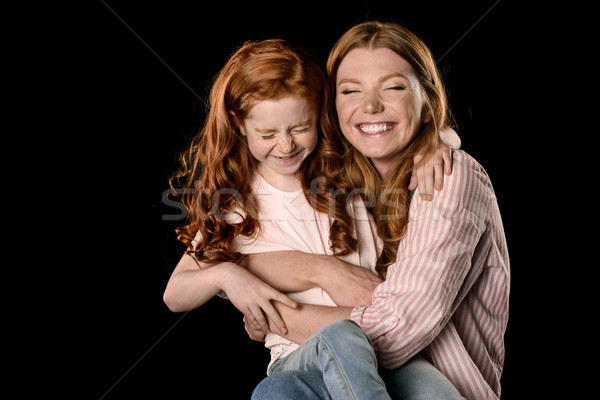 Beautiful redhead mother and daughter having fun together isolated on black Stock photo © LightFieldStudios