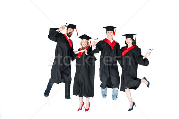 happy young students in graduation caps with diplomas jumping isolated on white Stock photo © LightFieldStudios
