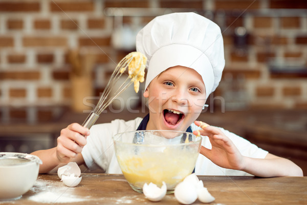 little boy in chef hat making dough for cookies Stock photo © LightFieldStudios