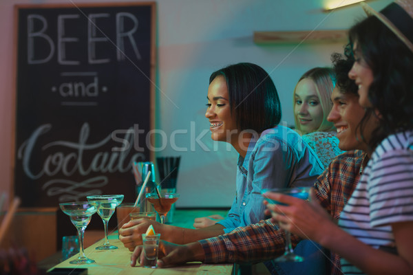 smiling multicultural friends in bar Stock photo © LightFieldStudios