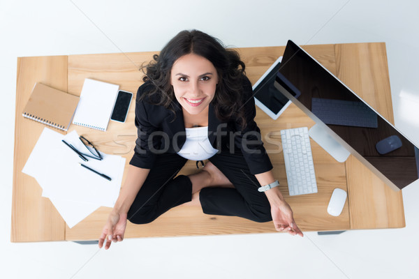 pregnant businesswoman on table in lotus pose Stock photo © LightFieldStudios