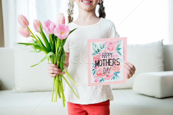 partial view of smiling girl holding tulips bouquet and postcard on mother's day holiday Stock photo © LightFieldStudios