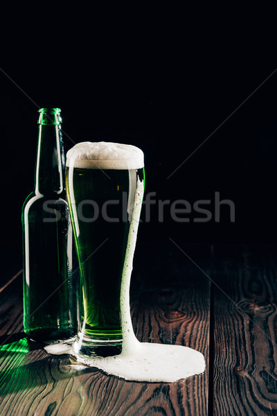 glass and bottle of green beer on wooden surface, st patricks day concept Stock photo © LightFieldStudios