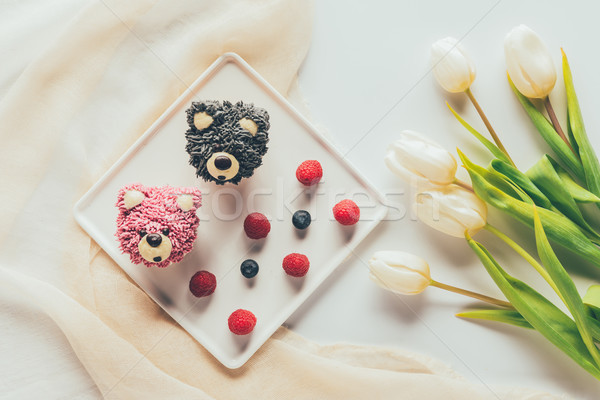 top view of delicious muffins in shape of bears, fresh berries and tulip flowers   Stock photo © LightFieldStudios