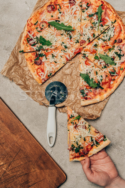 Close-up view of hand taking a slice of pizza on light background Stock photo © LightFieldStudios
