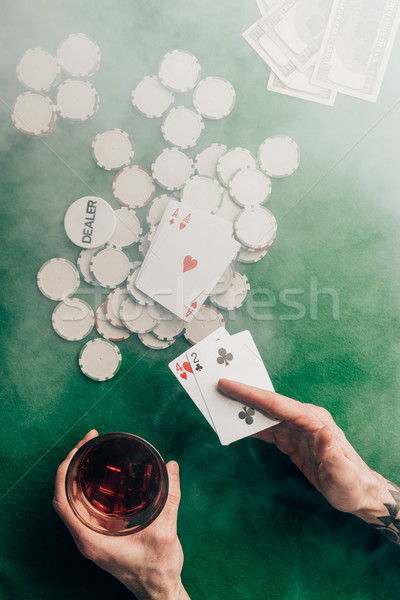 Man with whiskey and poker cards by casino table Stock photo © LightFieldStudios