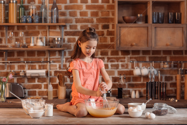 'Girl sitting on table and mixing ingredients for dough for cake Stock photo © LightFieldStudios