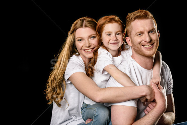 portrait of happy family in white t-shirts hugging each other isolated on black Stock photo © LightFieldStudios