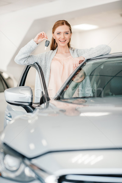 Happy woman holding car key and standing at car in dealership salon    Stock photo © LightFieldStudios