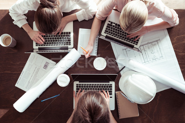 overhead view of businesswomen working at table on new architectural project Stock photo © LightFieldStudios