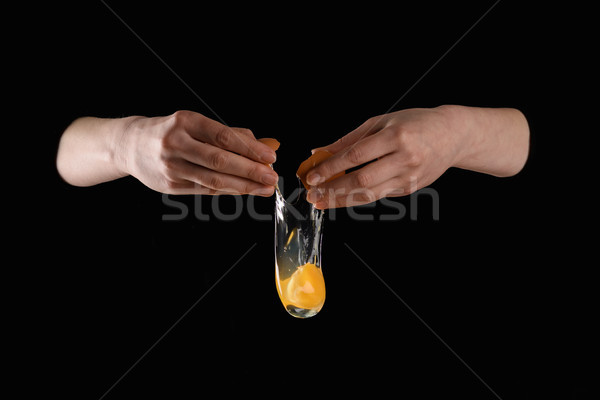 cropped image of woman dropping chicken egg isolated on black Stock photo © LightFieldStudios