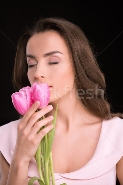 Beautiful young woman with closed eyes smelling pink tulips on black, international womens day conce Stock photo © LightFieldStudios