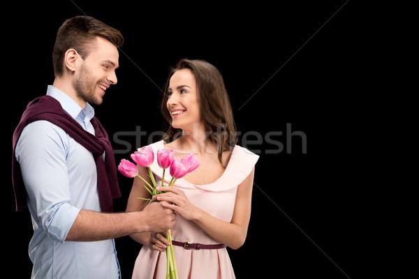 portrait of smiling man presenting tulips bouquet to happy woman on black, international womens day  Stock photo © LightFieldStudios