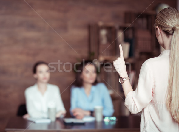 businesswoman gesturing and telling something to colleagues in office  Stock photo © LightFieldStudios