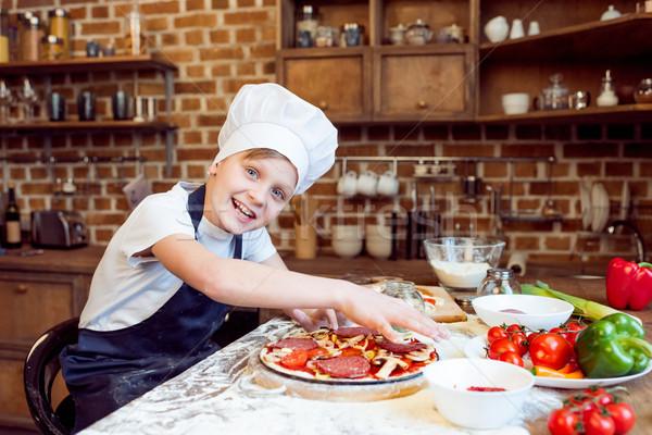 side view of little smiling boy making pizza Stock photo © LightFieldStudios