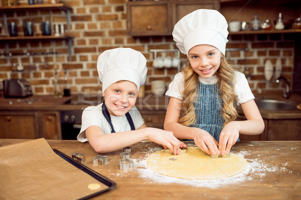 little kids in chef hats making shaped cookies in kitchen Stock photo © LightFieldStudios