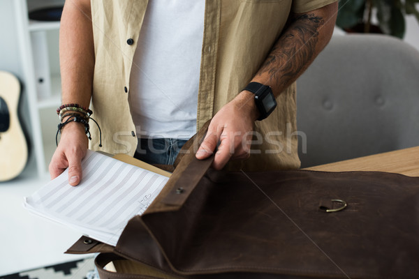 musician putting music notebook into bag Stock photo © LightFieldStudios