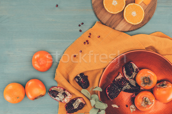 top view of persimmons with oranges and pomegranates on turquoise table Stock photo © LightFieldStudios