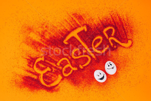 top view of easter sign made of red sand with chicken eggs with smileys on orange Stock photo © LightFieldStudios