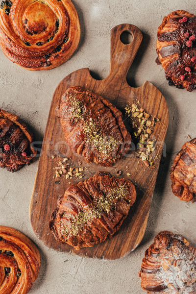 Flat lay with freshly baked sweet croissants with pistachio nuts on wooden cutting board on light su Stock photo © LightFieldStudios