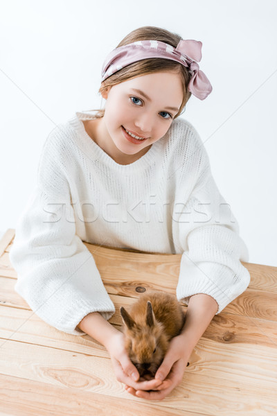 beautiful little girl smiling at camera while holding cute furry rabbit Stock photo © LightFieldStudios