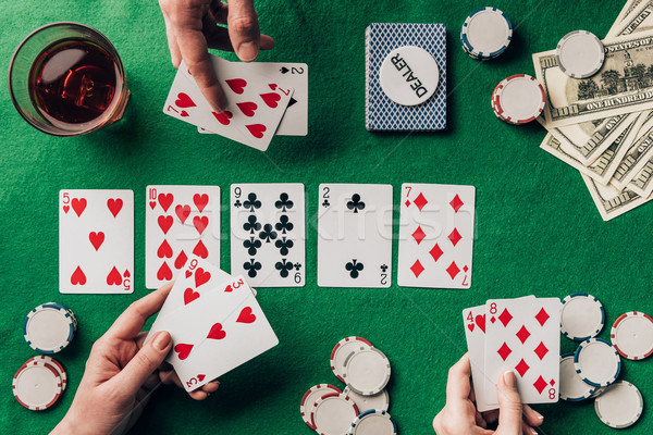 People playing poker by casino table with cards and chips Stock photo © LightFieldStudios