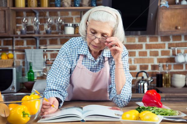 Starszy kobieta książka kucharska poważny patrząc posiedzenia Zdjęcia stock © LightFieldStudios