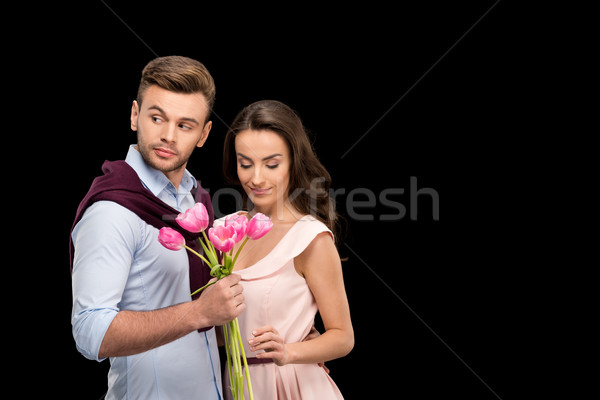 portrait of man with tulips bouquet looking away while hugging woman on black, international womens  Stock photo © LightFieldStudios