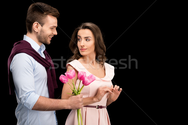 portrait of smilig man presenting tulips bouquet to woman on black, international womens day concept Stock photo © LightFieldStudios